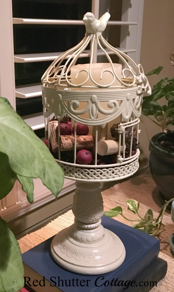Birdcage filled with pinecones, corks and cranberry balls. www.redshuttercottage.com