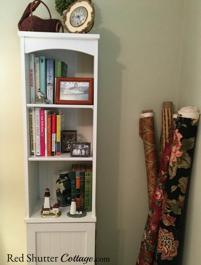 Close view of a small white storage unit holding books and tchotchkes in my Home Office. www.redshuttercottage.com