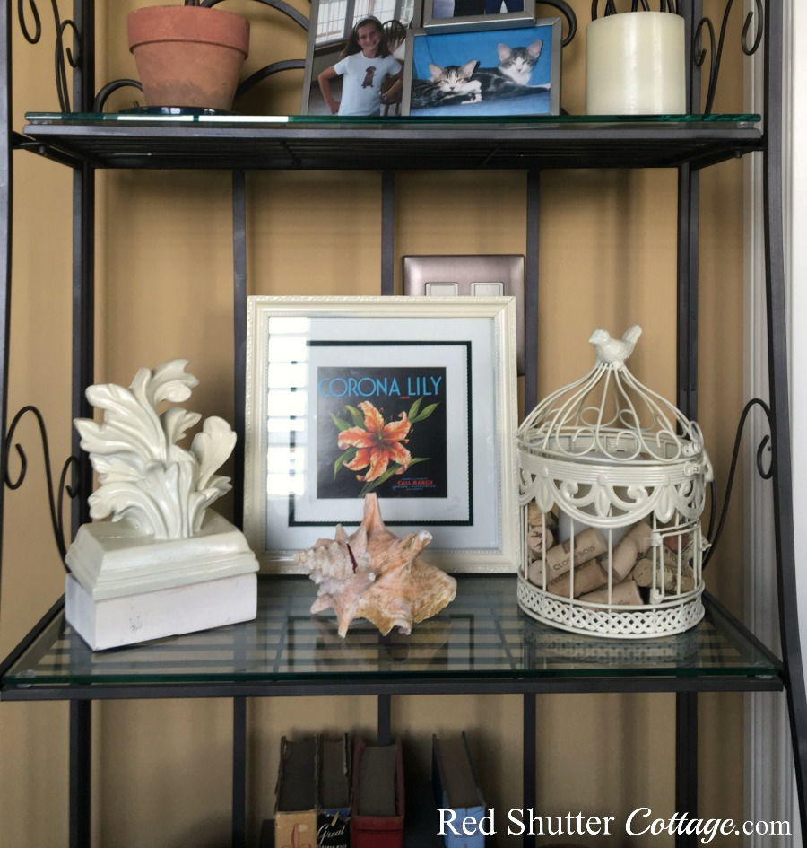 Renovated birdcage sitting on baker's rack shelf. www.redshuttercottage.com