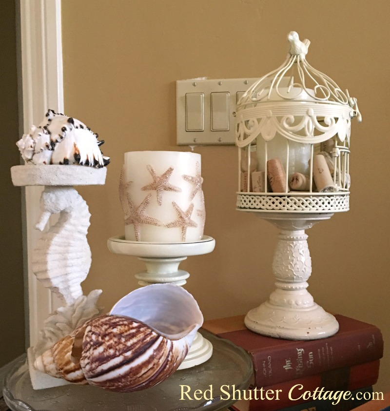Renovated birdcage in a summery vignette with shells. www.redshuttercottage.com