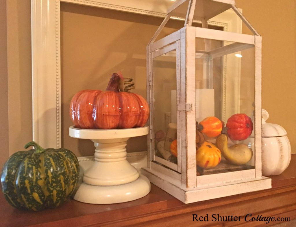 A mantel vignette incorporating gourds, a pumpkin on a candleholder, and a lantern filled with small pumpkins. www.redshuttercottage.com