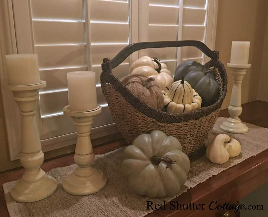 Fall pumpkins in basket with candles and runner. www.redshuttercottage.com