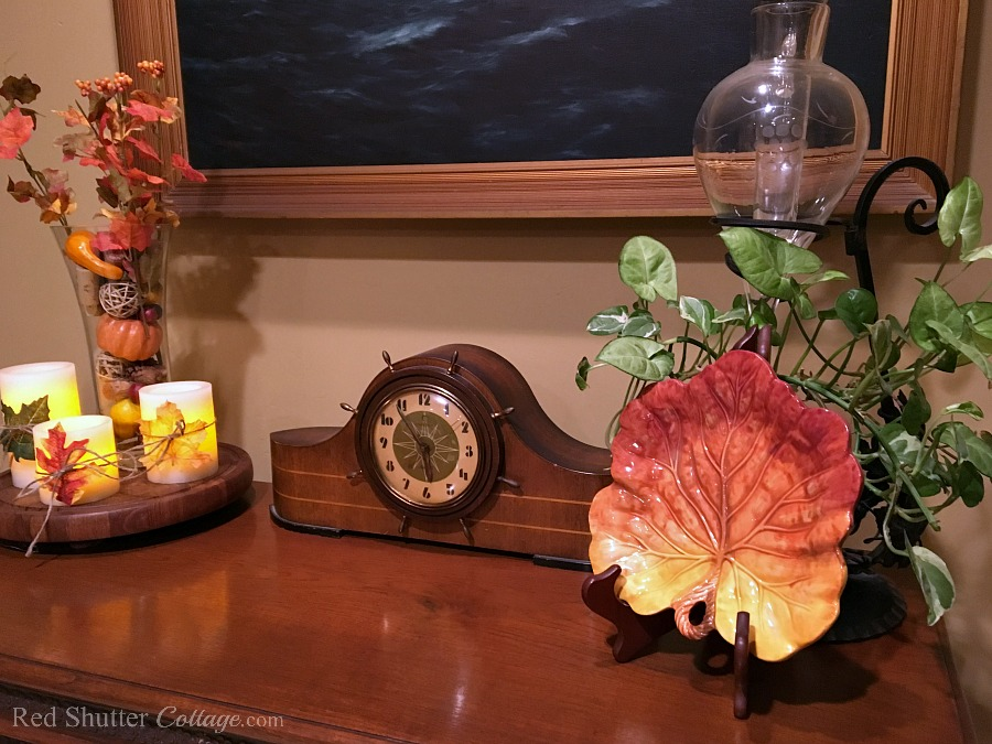 Our entry way bar. with the ships clock, decorated with candles and fall fruit for Fall 2017. www.redshuttercottage.com
