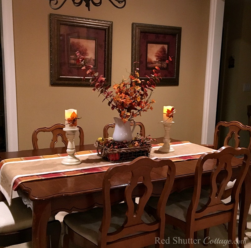 A front view of our fall 2016 dining room table with white pitcher and leaves on candles. www.redshuttercottage.com