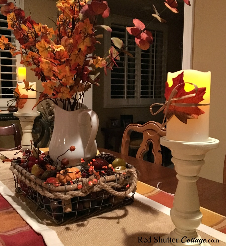 A side view of our 2016 fall dining table showing the white pitcher and basket filled with fall fruit. www.redshuttercottage.com