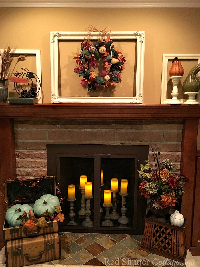 A view of our Fall 2017 mantel with wreath and candles in the fireplace. www.redshuttercottage.com