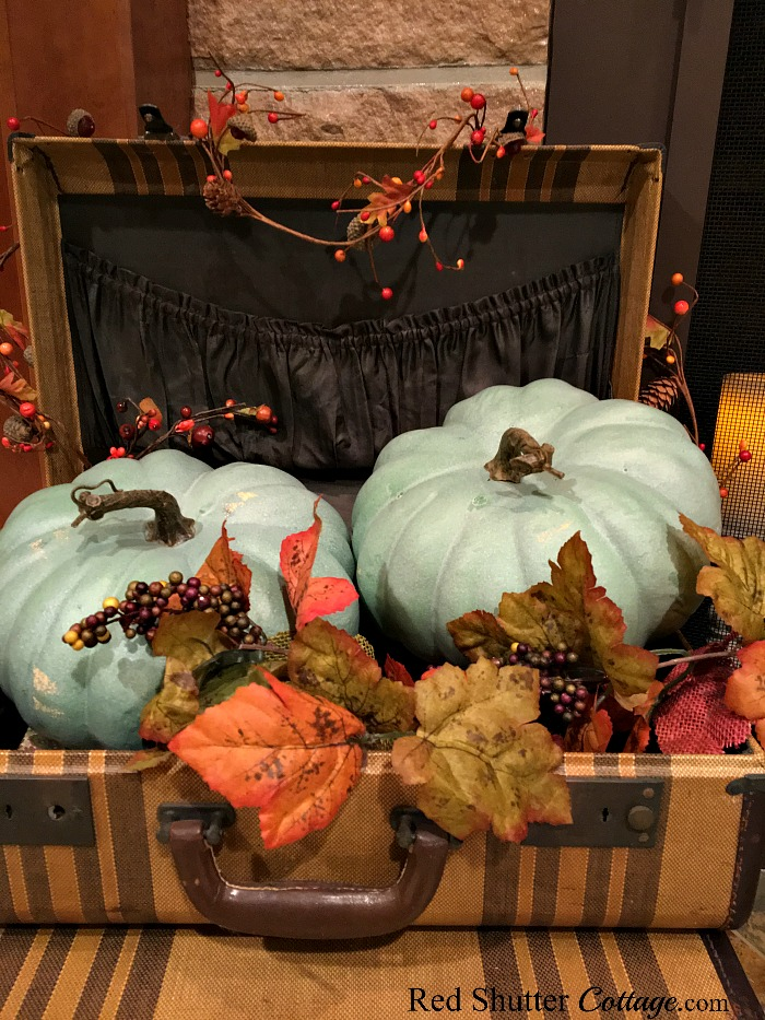 Two teal pumpkins on the hearth, nestled into a suitcase with berries and leaves. www.redshuttercottage.com