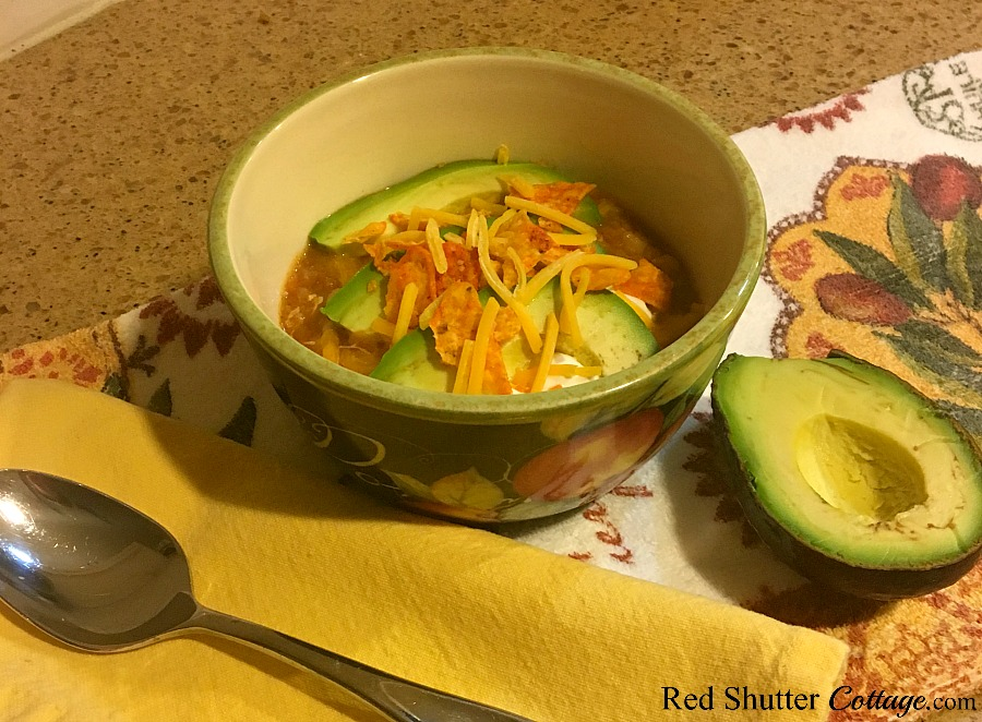 Tortilla soup in a bowl complete with avocado, chips and cheese. www.redshuttercottage.com