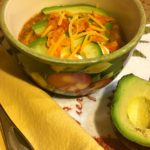 Chicken tortilla soup in a bowl with avocado, chips and cheese. www.redshuttercottage.com