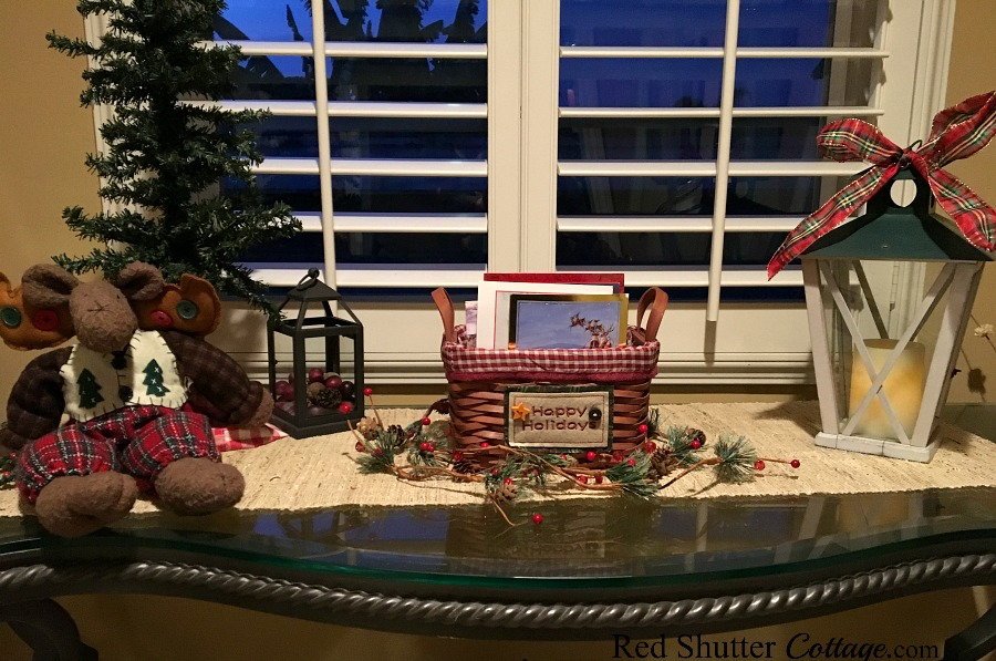 Christmas 2017 table vignette with Christmas card basket, moose with a Christmas tree and lantern with plaid bow. www.redshuttercottage.com