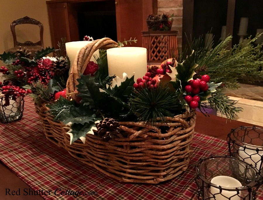 Christmas 2017 rustic Christmas basket on plaid runner with greenery and candles. www.redshuttercottage.com