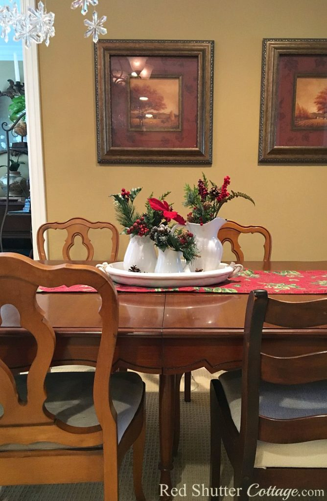 Christmas 2017 view of dining table with vignette of white pitchers and greenery. www.redshuttercottage.com