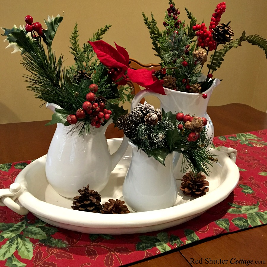 Christmas 2017 dining table vignette with white pitchers and greenery. www.redshuttercottage.com