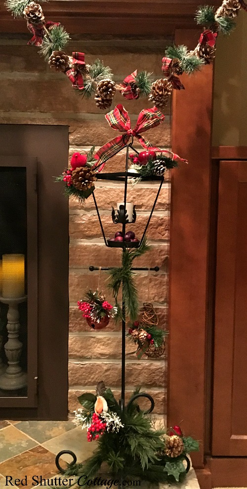 Christmas 2017 wrought iron lamppost with pine cone garland and Christmas picks. www.redshuttercottage.com