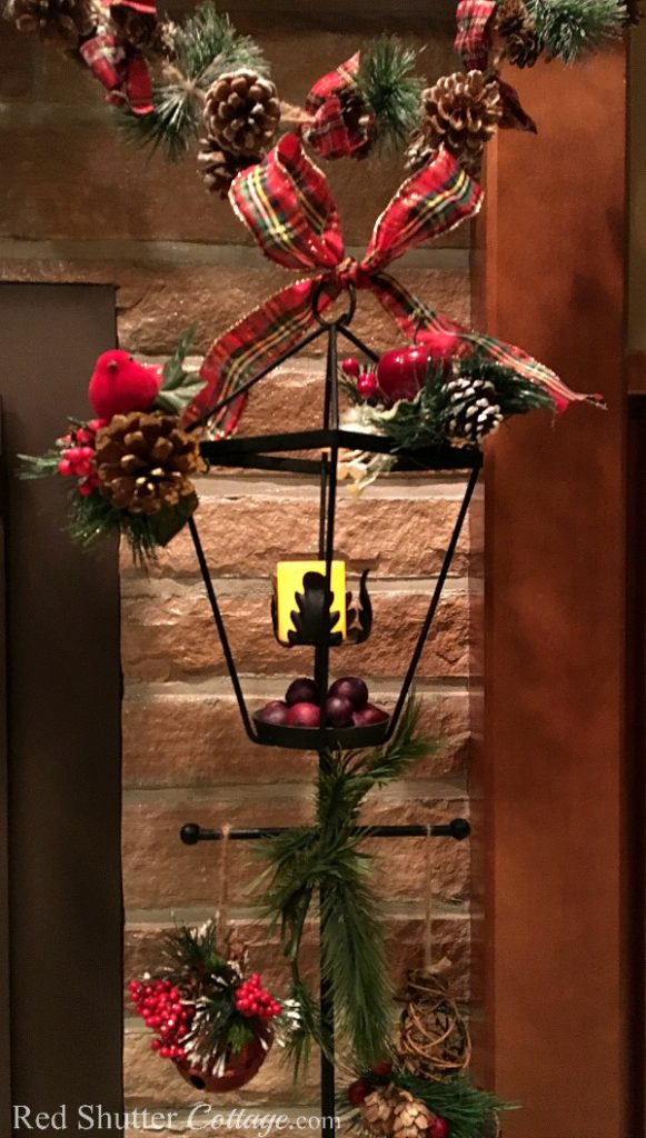 Christmas 2017 wrought iron lamppost with candle, greenery and plaid bow. www.redshuttercottage.com