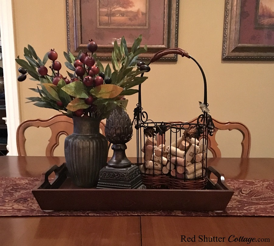 A wine basket, finial and pewter pitcher make up a winter dining table vignette. www.redshuttercottage.com