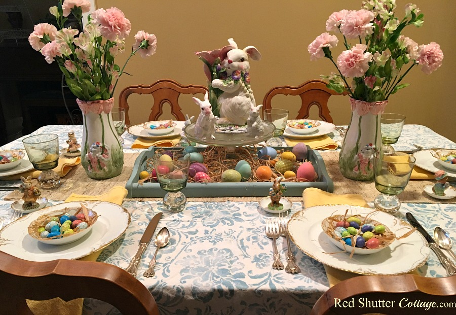 A Spring / Easter table setting including a nest of (candy) eggs sitting in a basket of raffia. www.redshuttercottage.com