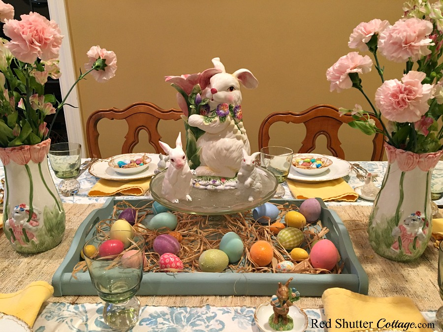 A whimsical Spring / Easter dining table showcasing a turquoise tray filled with raffia and pastel colored Easter Eggs. www.redshuttercottage.com