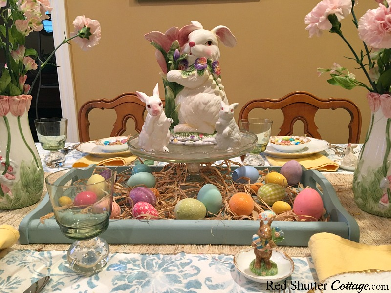 A whimsical Spring / Easter table setting with a bunny figurine sitting on top of a cake plate. www.redshuttercottage.com