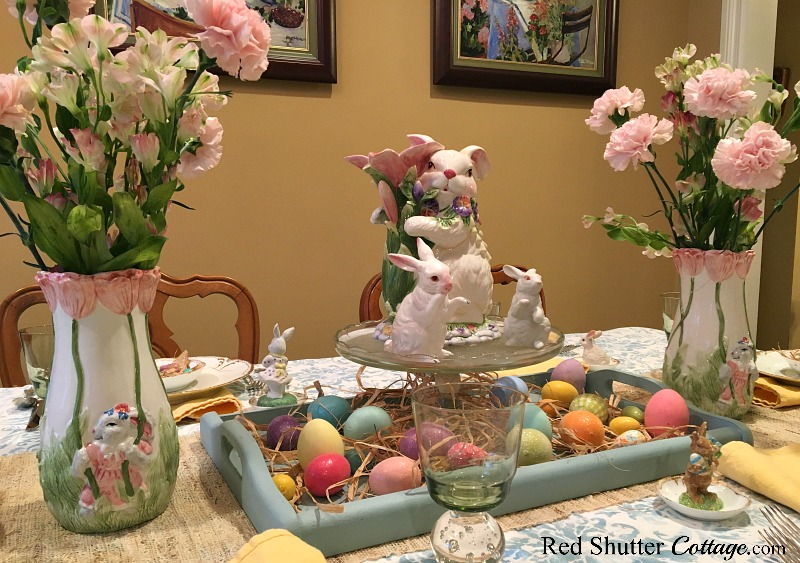 A whimsical Spring / Easter table setting, including pink carnations in Easter vases. www.redshuttercottage.com