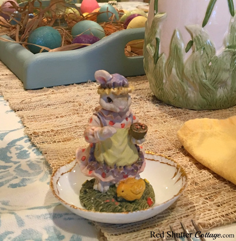 A close-up of a miniature bunny feeding a baby chick as part of the whimsical Spring / Easter dining table setting. www.redshuttercottage.com