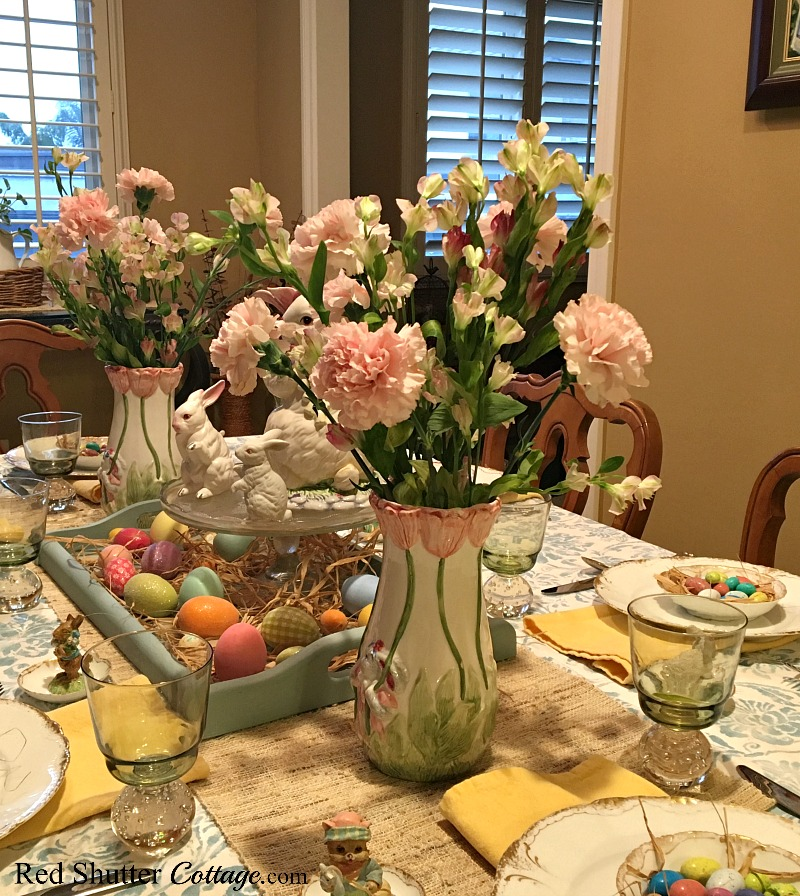 A close up view of a whimsical Spring / Easter table showing pink carnations in a vase. www.redshuttercottage.com