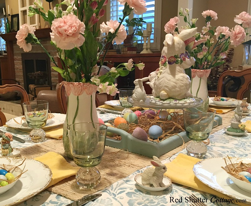 A back side view of a whimsical Spring / Easter table setting, including small miniature woodland creatures. www.redshuttercottage.com