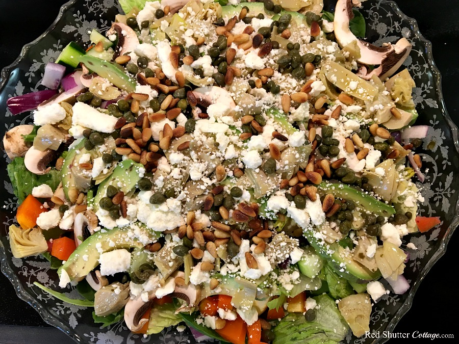 The third and final layer of the Mediterranean Chicken Salad calls for feta cheese, toasted pine nuts, and capers. www.redshuttercottage.com