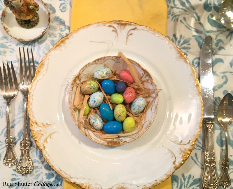 A close up view of a birds nest at the place settings of a whimsical Spring / Easter table setting. www.redshuttercottage.com