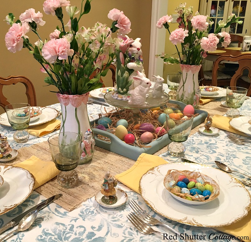 A whimsical Spring / Easter table set with a turquoise print tablecloth and bright yellow napkins. www.redshuttercottage.com