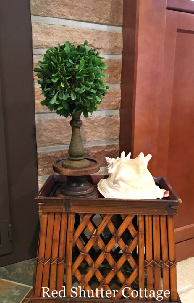 Summer hearth with topiary and small conch; How to Decorate a Summer Mantel.