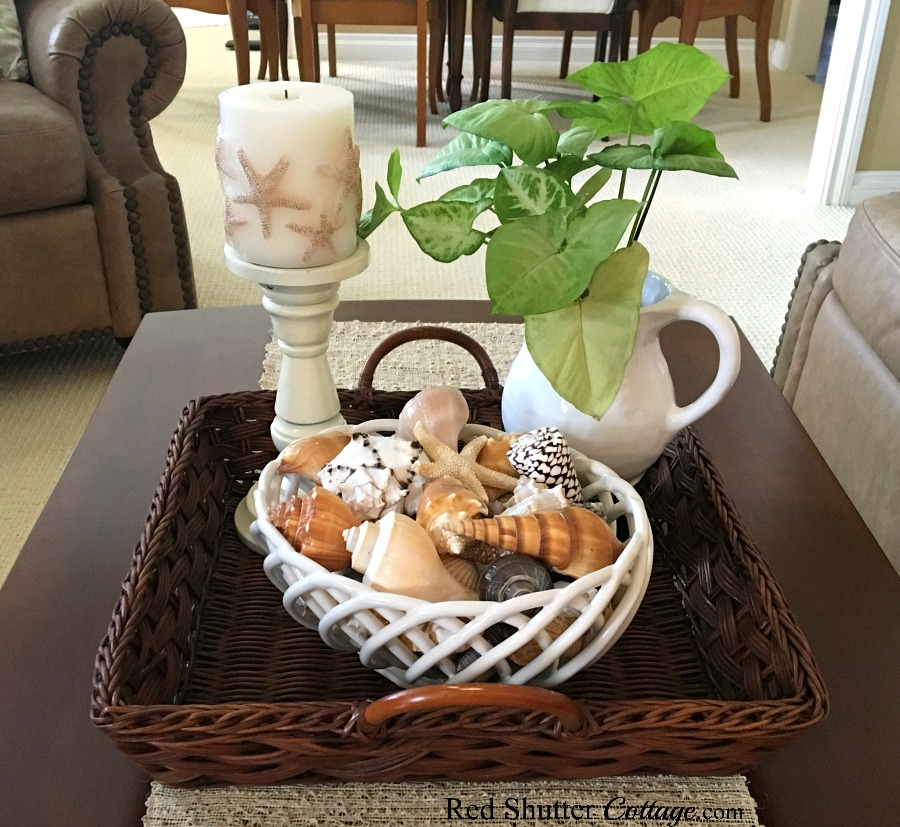 A Starfish candle, plant and bowl of shells complete the vignette of the Summer Coffee Table vignette. www.redshuttercottage.com