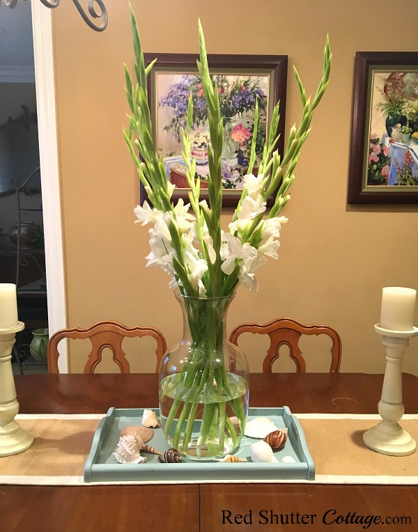 A dining table with gladiolas sitting in an aqua blue tray in a bright and easy summer living room. www.redshuttercottage.com