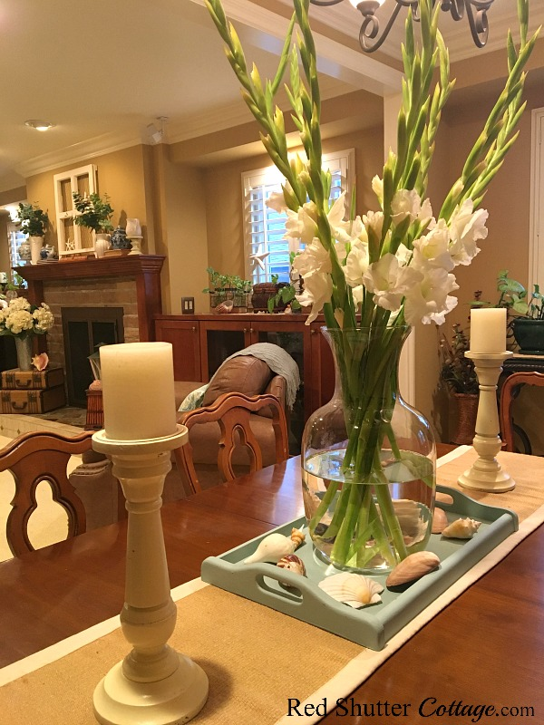 A view of the dining table with gladiolas in a tray with sea shells and candles. www.redshuttercottage.com