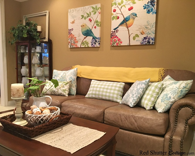 A couch and coffee table in summer colors in a bright and easy summer living room. www.redshuttercottage.com