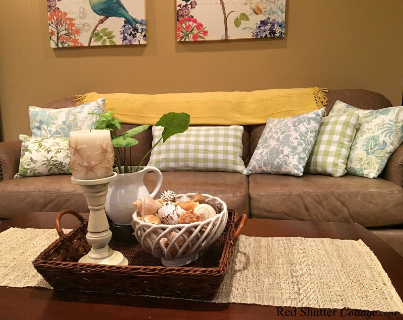 A couch decorated with summery pillows in a bright and easy summer living room. www.redshuttercottage.com
