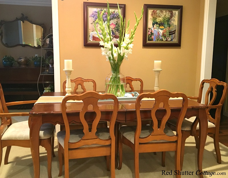 A summer table with prints and gladiolas in a bright and easy summer living room. www.redshuttercottage.com