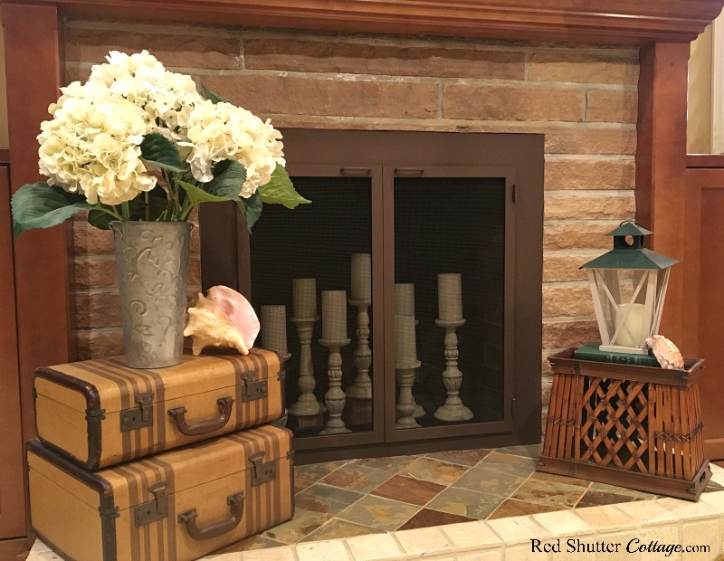 Hydrangeas, shells and a lantern on the hearth in a bright and easy summer living room. www.redshuttercottage.com