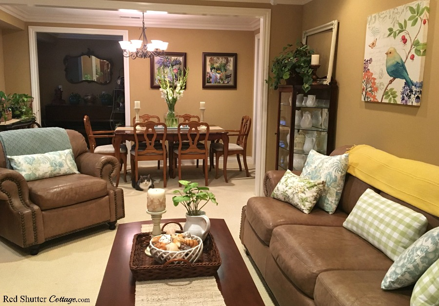A bright and easy summer living room view including the couch and dining table. www.redshuttercottage.com