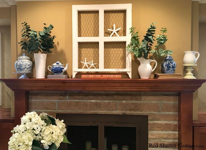 A window on the mantel in a bright and easy summer living room. www.redshuttercottage.com