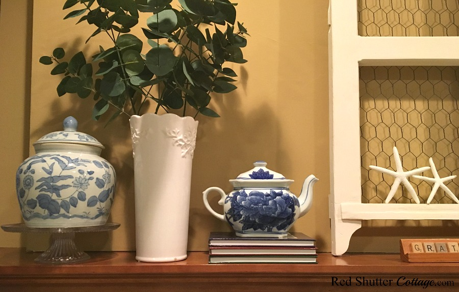 A summer mantel with blue & white ceramic ware in a bright and easy summer living room. www.redshuttercottage.com