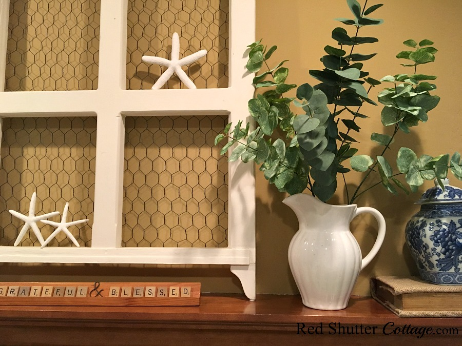 A mantel with a pitcher of leaves and starfish in the window of a bright and easy summer living room. www.redshuttercottage.com