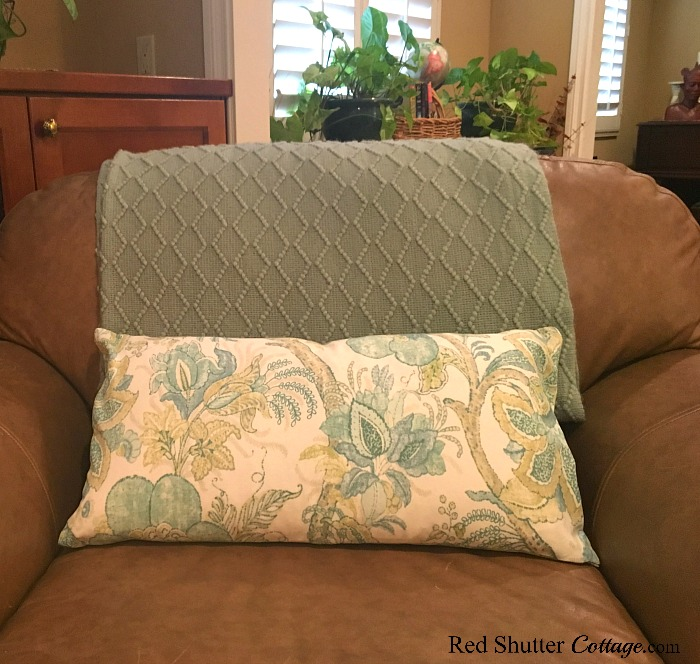 A lumbar pillow covered in a summer print, in a bright and summery living room. www.redshuttercottage.com