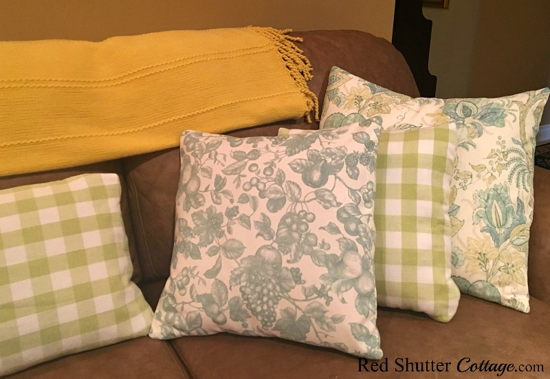 A close up of check and floral summer pillows in a bright and summer living room. www.redshuttercottage.com