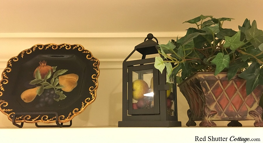 The left side of the spring vignette of how to decorate a plate shelf over the sink includes a plate decorated with pears and a lantern filled with pears. www.redshuttercottage.com