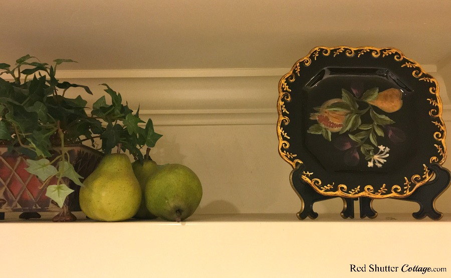 On the right hand side of the spring vignette of how to decorate a plate shelf over the sink, a group of pears, an ivy plant and a plate with pear decorations complete the scene. www.redshuttercottage.com