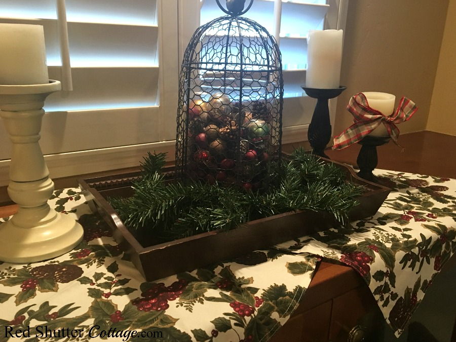 Styling window countertops for Christmas included 2 napkins as runners and a chicken wire cloche filled with pine cones, berries and ornaments. www.redshuttercottage.com