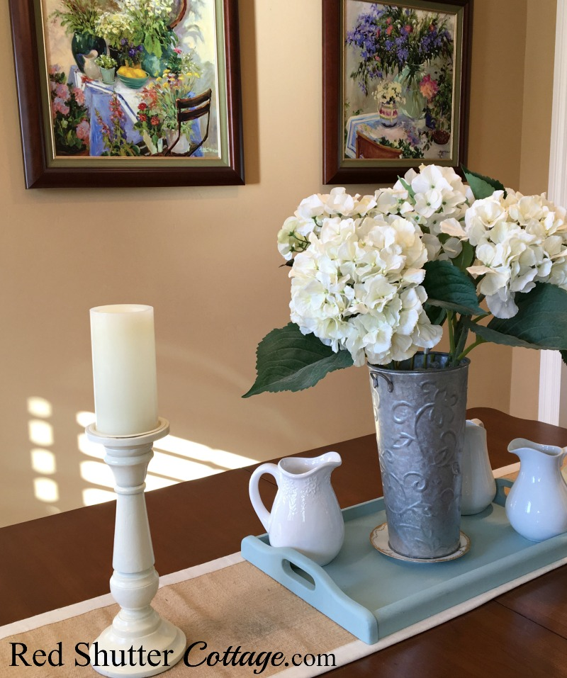 Summer dining room table with candles, pictures and hydrangeas. www.redshuttercottage.com