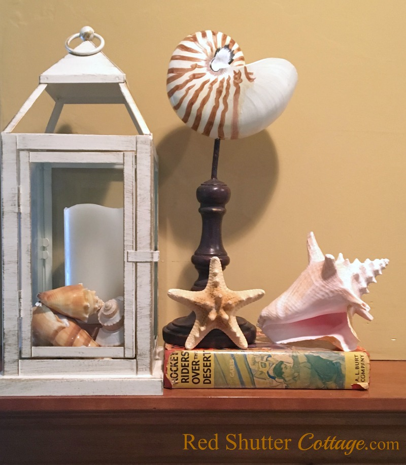 Summer living room view of mantel with books, shells and lantern. www.redshuttercottage.com