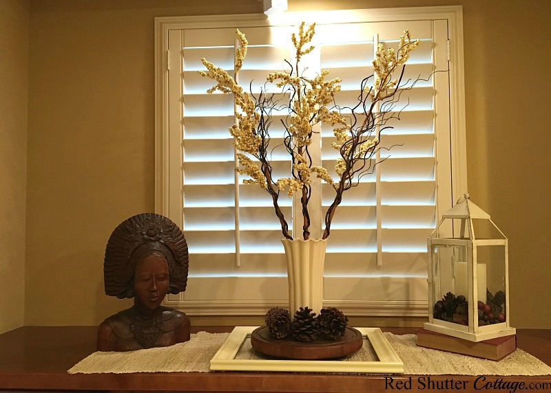 This winter version of styling window countertops includes branches in a vase and a mahogany bust. www.redshuttercottage.com